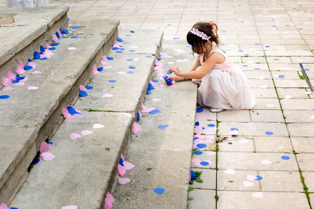 kid playing with confetti after a religious wedding in luxembourg