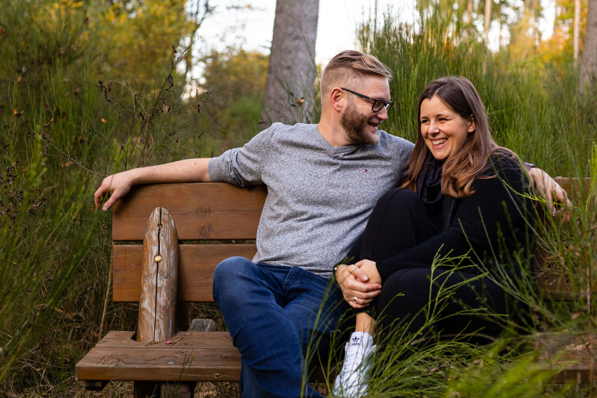 Couple laughing on a bench in the forest