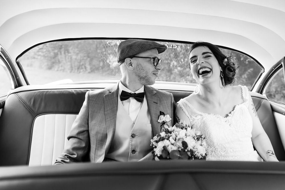 bride and groom laughing in their vintage wedding car